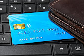 Credit card with a wallet on the keyboard of laptop. Buying in the online store