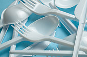 Plastic cutlery, forks, spoons and knives. Pollution of the environment with plastic and microplastics. Blue background