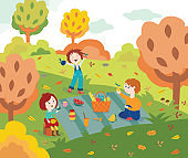 Children friends at picnic outdoors in autumn park or garden with colorful tree leaves.