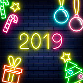 Vector illustration of 2019 New Year banner with glowing neon sign and holiday decorations.