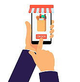 Online grocery shop app on mobile phone. Internet purchase of food in paper bag