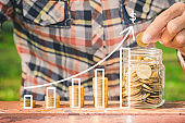 business hand put coin stack with statistic chart growing profit success.