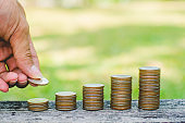 man put coins stack on wood table in park with sunrise. business budgeting financial banking saving and startup concept success increase growing investment.