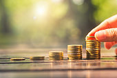 investor business woman hand putting golden coins stack on wood table with blur nature bokeh background in park with sunrise financial banking saving and startup concept success growing investment.