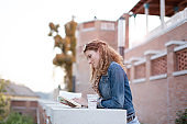 Young urban woman reading book outdoors