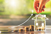 loan investment residential building house, real estate, property, mortgage concept. hands put coin in glass jar on wood table in park with chalk draw graph growth up and souse. home sweet home.