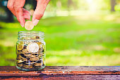 businessman putting coin in to glass jar count the money for saving concept. budgeting for investment startup business.