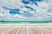 wood table with tropical beach and sea summer and blue sky with cloud background. beautiful floor copy space for design your products brand for ad.