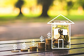 loan investment residential building , real estate, property, mortgage concept. stack coin with currency and coin in glass on wood table in park. startup graph growth up and house. ESG.