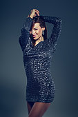 Young celebrity woman in glitter dress dancing