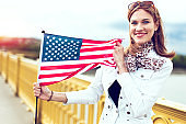 Young fashionable patriot woman with toothy smile stretching USA flag in sunset
