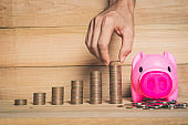 hand put coin keep money stack on wood table with pink piggy bank. financial saving concept.