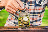 businessman putting coin stacking in to glass jar count the money for saving concept. budgeting for investment startup business.