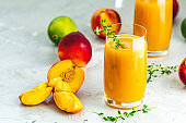 Glass of fresh healthy peach smoothie or juice on light gray concrete surface table