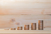 coin stack on wood table with wooden background. money saving and financial investment concept.