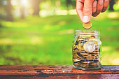 golden coins stack with handsome man hands but coin to jar on wood table with blur nature bokeh background in park. financial saving money concept. ESG Environmental Social Governance. startup.