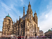 Crowd of tourist travel in shopping street in center of Vienna with Domkriche St. Stephan church in Vienna, Austria, Europe