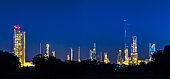 petrochemical and petroleum plant industry with refinery stack and tank farm in in chemical industrial zone at night after sunset