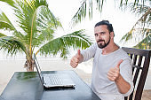 Vacation and technology. Work and travel. Young bearded man using laptop computer while sitting at beach cafe bar and showing thumbs up