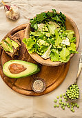 Fresh delicious green salad with avocado in a wooden plate and gluten free toast. Top view. Healthy lunch dish and Diet detox food concept.