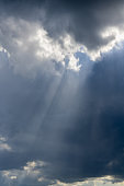 Beautiful vertical cloudscape with sunrays shining through the dark clouds