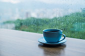 Coffee cup on wooden table with rain drops background