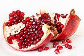 open pomegranate fruit on plate on white