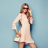 Blonde young woman in coral spring summer dress