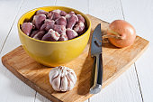 Chicken hearts in a yellow bowl on a cutting board. Near the bulb of garlic, one onion and a knife. Useful diet food. Health care.