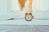 Close up of alarm clock at 6 o'clock in the morning and blurred woman waking up in her bedroom