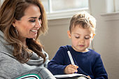 Mother teaching her son how to draw