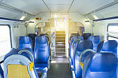 Salon inside of the speed commuter train with empty seats staircase to the second floor.
