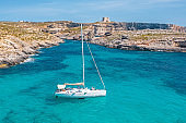 Luxury white yachts colorful landscape with bay, azure water, rocky beach, blue sky, aerial view.
