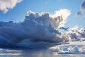 Powerful cumulonimbus dark cloud with heavy rain, tropical rain. Around the clear blue sky and the rising sun.