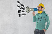 the construction worker holds a megaphone in his hands, the concept of issuing orders