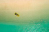 Aerial view of slim woman swimming on the swim mattress in the transparent turquoise sea in Seychelles. Summer seascape with girl, beautiful waves, colorful water. Top view from drone