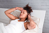 Black woman feeling sick and uncomfortable in bed