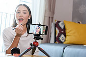 Beauty blogger demonstrating how to apply eyeliner and review products on live broadcast for social media by smartphone, life of an influencer