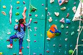 A young girl climbing a tall, indoor, man-made rock climbing wall