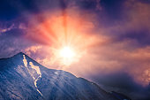 Sun through the dramatic sky over the mountains of Denali National Park