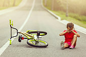 A little girl riding a bicycle. the bike accident. Sit crying on the street