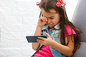 Little girl crying and holding smartphone.The little girl hid her face and cried, holding a mobile phone in her hands.