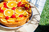 Orange and cherry pie on a checked cloth for picnic