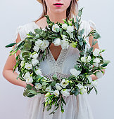 Beautiful woman with white roses wreath on white background