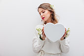 woman with white roses holding a heart shape gift box.