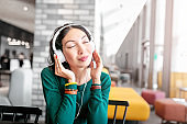 Happy asian woman enjoying the music by headphones and relax in hotel hall or cafe