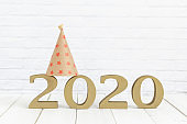 2020 new year and party hat on white wood table over white background with copy space