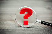 Red Question mark with magnifying glass on wood table