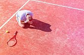 High angle view of disappointed mature man with head in hands while kneeling by tennis racket on red court during summer