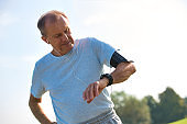 Active senior man standing with hands on hips while checking watch in park